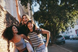 Outdoor shot of multi ethnic female friends walking outdoors in city and having fun. Three young women walking together, piggybacking and enjoying.