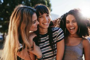 Close up portrait of smiling young women outdoors on city street. Mixed race female friends enjoying outdoors in the city.