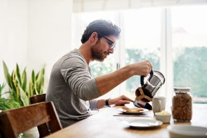 Shot of a young man using a digital tablet while having breakfast at home