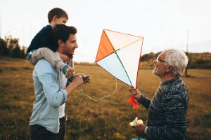 Photo of a three generations of men, who enjoy kite running and spending time together outdoors in the nature
