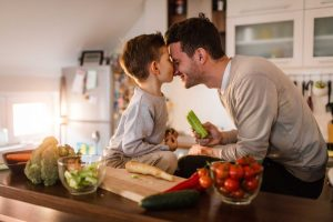 Father and son having fun in the kitchen while preparing healthy food