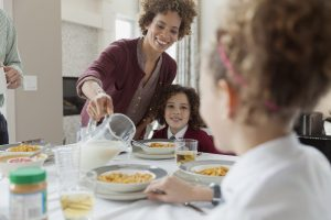 Mother pouring milk for daughters cereal.