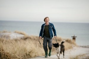 Photo of a man walking by the beach with his dog