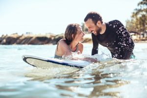 Loving couple of smiling surfers in the water, flirting while waiting for a good wave to come
