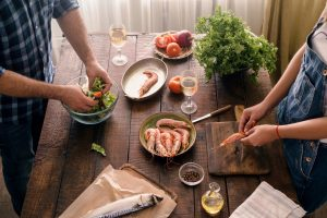 Top view couple cooking together shrimp dinner and salad of vegetables on a wooden table in home kitchen